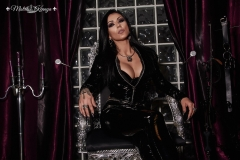 Mistress Kennya in PVC on her throne