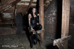 Mistress Kennya in leather with Her whip in Her dungeon