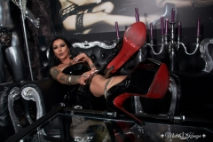 Mistress Kennya with her shoes out to be kissed by her slave