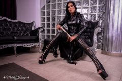 Mistress-Kennya-in-long-eather-dress-with-open-toe-boots-and-whip-MARKED