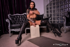 Mistress-Kennya-wearing-boots-sitting-on-a-pile-of-money-MARKED